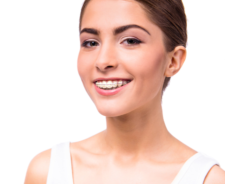 beautiful teeth: Portrait of a beautiful woman with braces on teeth, isolated on a white background