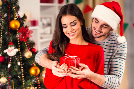 couples: Merry Christmas. Young couple celebrating Christmas at home
