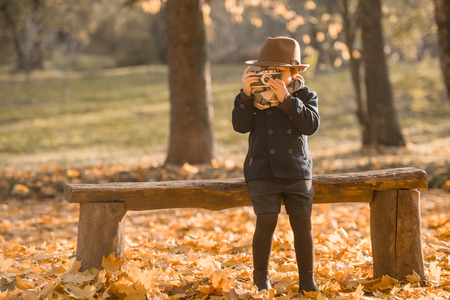camera: Little boy uses an old camera while walking in autumn park Stock Photo