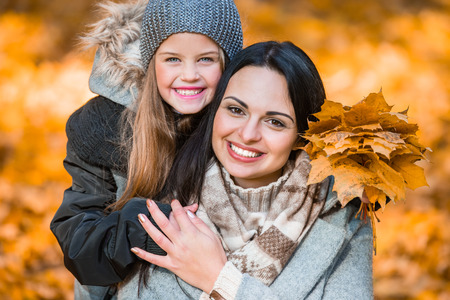 beautiful mother: Happy mother and daughter during a walk in the autumn park