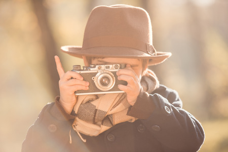 fashion boy: Little boy uses an old camera while walking in autumn park Stock Photo
