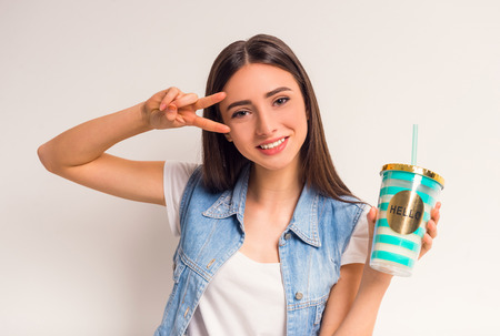 tomando jugo: Portrait of a cheerful teenager girl drinking juice on a white background Foto de archivo