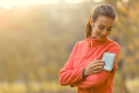 woman listening to music: Young beautiful woman running in autumn park and listening to music with headphones. Stock Photo