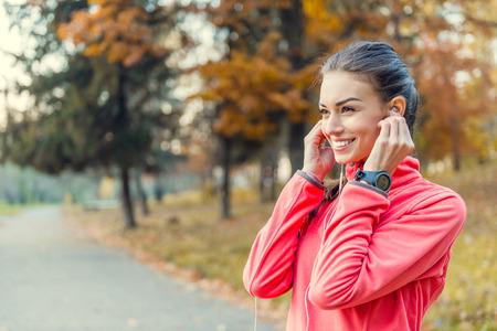 escucha activa: Mujer hermosa joven que se ejecuta en parque del otoño y escuchar música con auriculares.