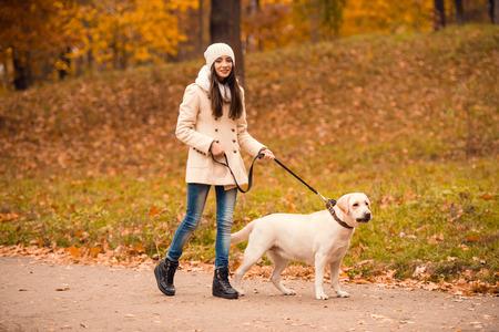 mujer con perro: Retrato de una mujer joven y hermosa con su perro mientras caminaba en el parque de otoño