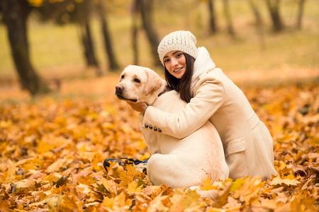 dog days: Retrato de una mujer joven y hermosa con su perro mientras caminaba en el parque de otoño