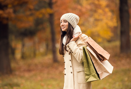 lifestyle outdoors: Portrait of a beautiful young woman with shopping bags for shopping while walking in the autumn park