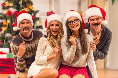 Quattro giovani amici, due ragazze e due ragazzi mentre festeggiano il Natale a casa Archivio Fotografico - 47909196