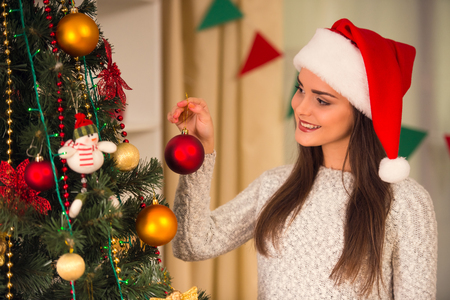 decorates: Young beautiful woman decorates Christmas tree celebrating Christmas at home Stock Photo