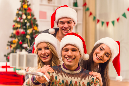 family and friends: Four young friends, two girls and two boys while celebrating Christmas at home