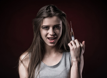 drug use: The social problem. Young unhappy woman holding a syringe to drug use