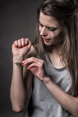 lacerate: The social problem. Young unhappy woman who wants to make a suicide, with blade Stock Photo