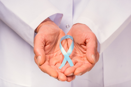 urologist: The social problem of male diseases. Close up of doctor hand with a blue ribbon. Isolated on white background Stock Photo