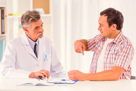 urologist: The social problem of male diseases. Portrait of doctor and patient man with a blue ribbon sitting in the office Stock Photo