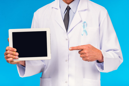 urologist: The social problem of male diseases. Portrait of doctor with blue ribbon holding the tablet. Isolation on blue background