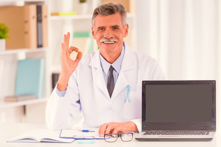 urologist: The social problem of male diseases. Portrait of doctor with blue ribbon sitting in his office Stock Photo