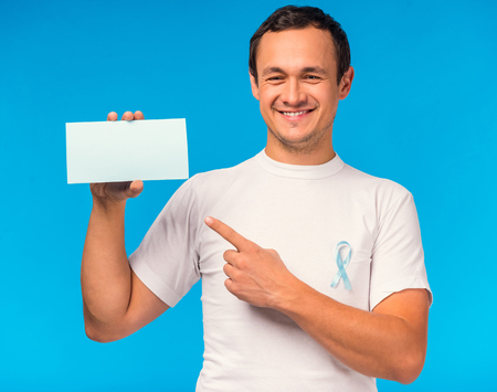 oncologist: The social problem of male diseases. Portrait of a man with a blue ribbon. Isolated on a blue background Stock Photo