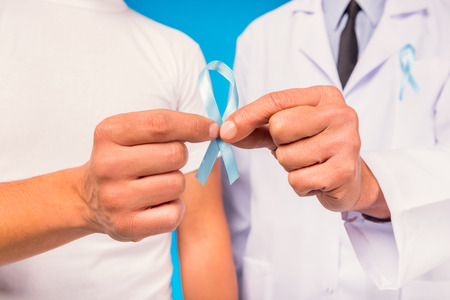 urologist: The social problem of male diseases. Portrait of doctor and patient man with a blue ribbon. Isolation on blue background