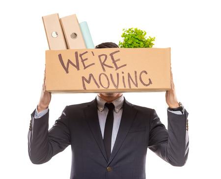 Junge glücklich Geschäftsmann mit Box für Umzug in ein neues Büro. Studio gedreht, isoliert auf weißem Hintergrund