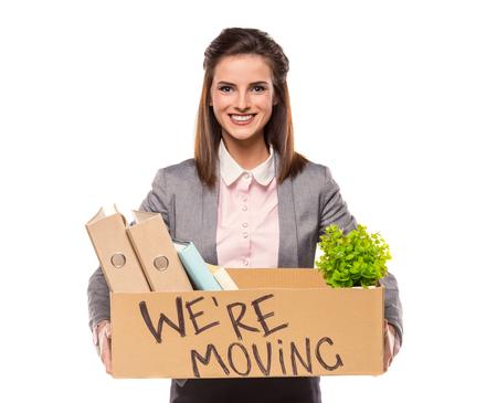 Junge glückliche Geschäftsfrau mit einem Kasten in ein neues Büro zu bewegen. Studio gedreht, isoliert auf einem weißen Hintergrund
