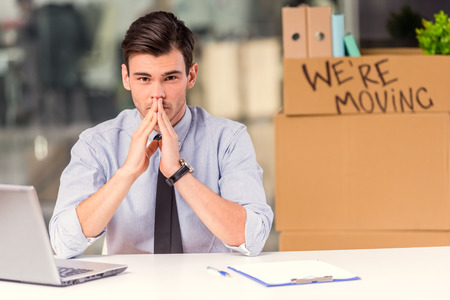 Young happy businessman with boxes to move to new office