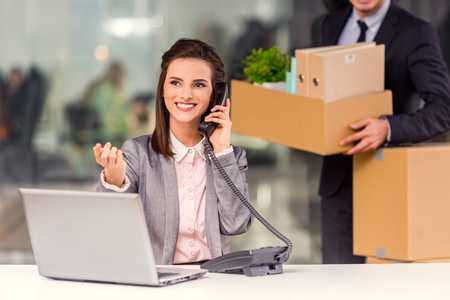 moving: Young happy businessman and a business woman with boxes for moving into a new office Stock Photo