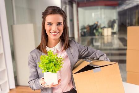 Jeune femme d'affaires heureux avec des boîtes pour le déplacement dans un nouveau bureau