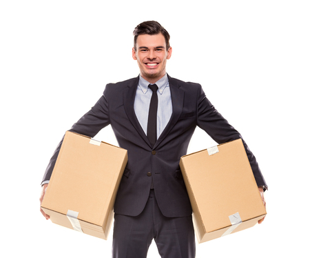 moving: Young happy businessman with box for moving into a new office. Studio shot, isolated on a white background