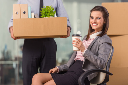 moving office: Young happy businessman and a business woman with boxes for moving into a new office Stock Photo