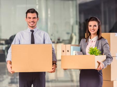 Jeune homme d'affaires heureux et une femme d'affaires avec des boîtes pour le déplacement dans un nouveau bureau