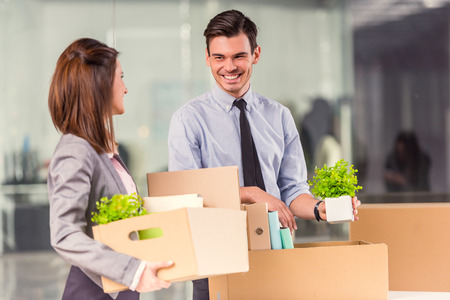 Young happy businessman and a business woman with boxes for moving into a new office Standard-Bild