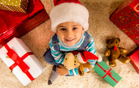 considers: Little boy considers gifts, while celebrating Christmas at home