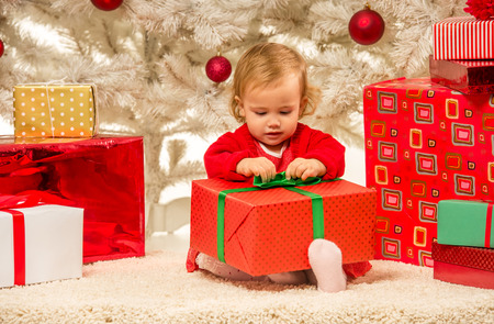 considers: The little girl considers gifts, while celebrating Christmas at home Stock Photo