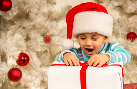 excitement: Little boy considers gifts, while celebrating Christmas at home