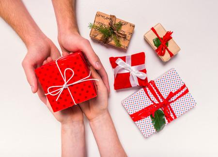 Hand hält Box für ein Geschenk auf einem weißen Hintergrund