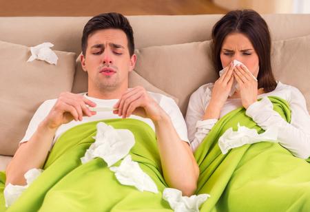 Ziekte. Een jong paar tijdens ziekte behandeling thuis Stockfoto