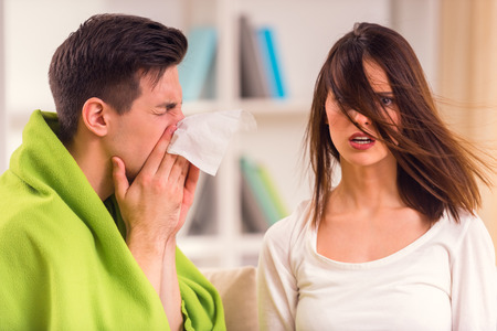 chory: Choroba. Młoda kobieta pomaga wyleczyć swojego przyjaciela w domu