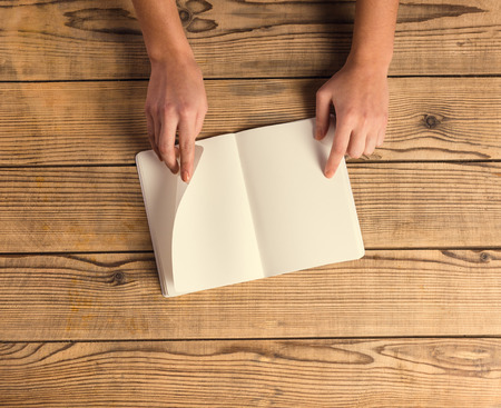 old desk: Hands close-up book to use notes on a wooden table