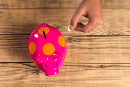 bank rate: Hands close up putting a coin into a pink pig on a wooden table Stock Photo