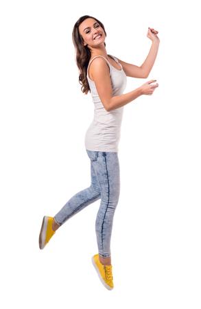 In voller Länge Foto von attraktiven Mädchen in der beiläufigen Kleidung, die Kamera und lächelt, während Springen, isoliert auf weiß photo