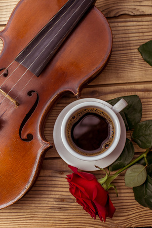 fiddlestick: Violin, coffee and rose close up lying on the wood table