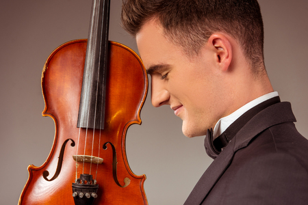 hombres guapos: The young musician man playing violin on gray background