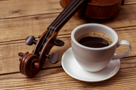 fiddlestick: Violin and coffee close up lying on the wood table