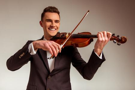 violoncello: Il giovane musicista che suona il violino su sfondo grigio