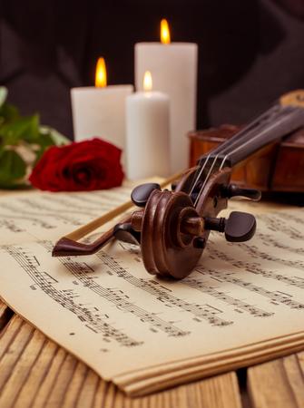 ヴァイオリンとノートは、木製のテーブルの上に横たわるを間近します。 写真素材