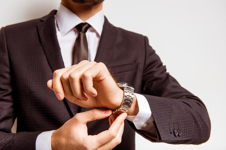 Portrait of a young successful businessman in a business suit, using the watch on a gray background