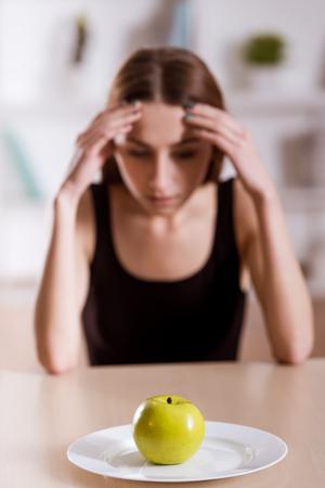 chica delgada se niega manzana que se encuentran en la placa blanca