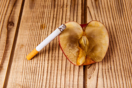 bad apple: Withered apple and cigarettes represent a bad influence on the human body