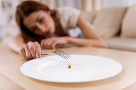 Girl exhausted from malnutrition lies on the sofa. Plate is empty side and closeup on the photo