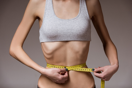 anorexia girl: Anorexia. Girl showing skinny waist with tape measure close-up